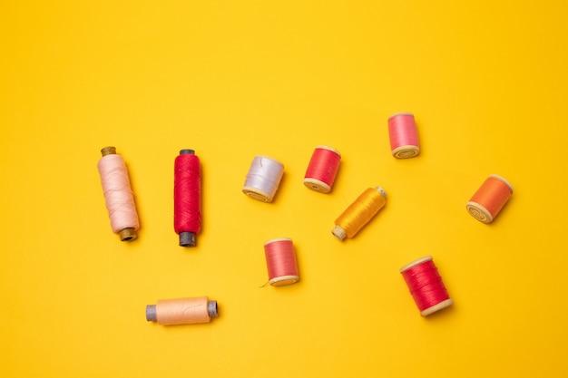Bobines de fil multicolores ou accessoires de couture sur fond jaune.