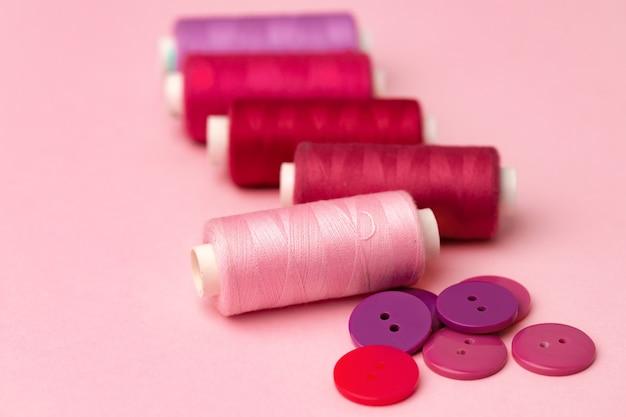 Bobines de fil multicolores et boutons sur surface rose
