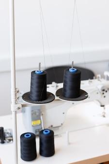 Bobines de fil noir près de la machine à coudre dans la production dans l'atelier de couture