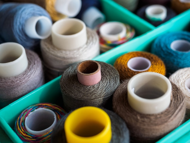 Bobines avec des fils de couleurs différentes pour la couture. fils situés dans la boîte. la vue du haut sur les fils à coudre.