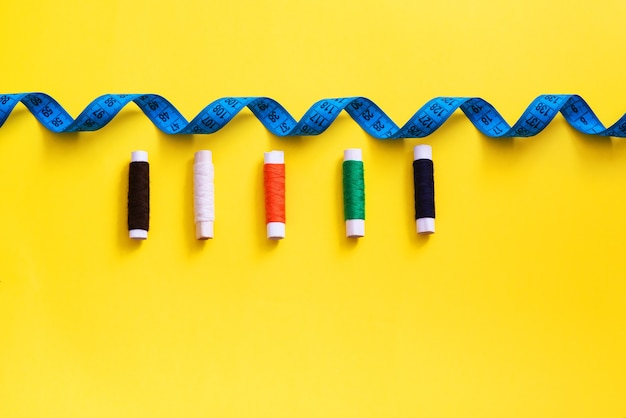 Bobines multicolores avec fils à coudre, mètre ruban sur fond clair
