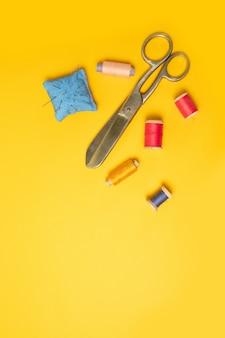 Bobines roses de fils multicolores, ruban à mesurer, aiguilles de machine à coudre sur un fond. accessoires de couture pour travaux d'aiguille, couture.