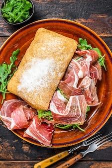 Bocadillo de jamon espagnol, sandwich au jambon serrano sur pain ciabatta avec roquette. fond en bois sombre. vue de dessus.
