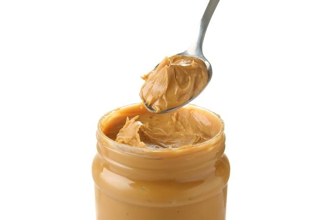 Bocal et cuillère avec du beurre d'arachide savoureux sur blanc