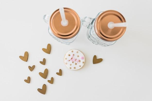 Bocal mason transparent avec cookie d'amour et formes de coeur sur fond blanc