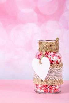 Un bocal en verre avec des coeurs colorés sur fond rose avec bokeh