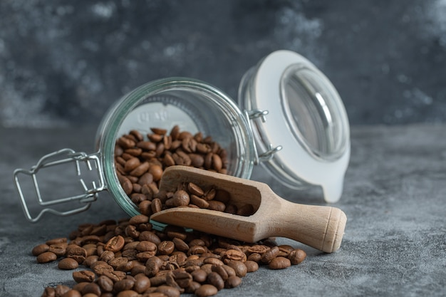 Un bocal en verre avec une cuillère en bois pleine de grains de café