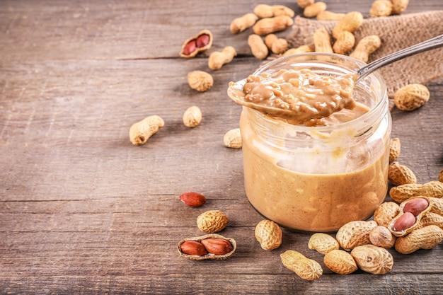 Bocal en verre et cuillère pleine de beurre d'arachide croquant aux arachides en bref à proximité sur bois