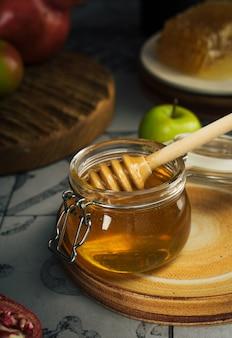 Bocal en verre avec du miel frais cuillère à miel pomme et grenade nouvel an juif rosh hashanah