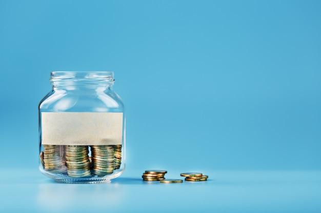 Un bocal en verre avec des pièces et un autocollant avec un espace libre pour le texte, sur bleu.