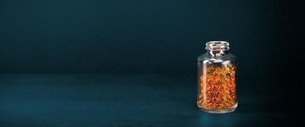 Un bocal en verre avec des pilules de couleur jaune orange vif sur fond bleu