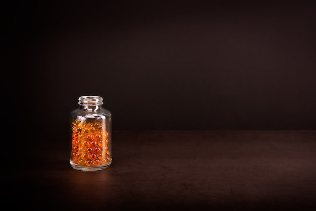 Un bocal en verre avec des pilules de couleur jaune orange vif sur fond marron