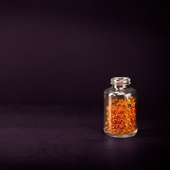 Un bocal en verre avec des pilules de couleur jaune orange vif sur un mur lilas.