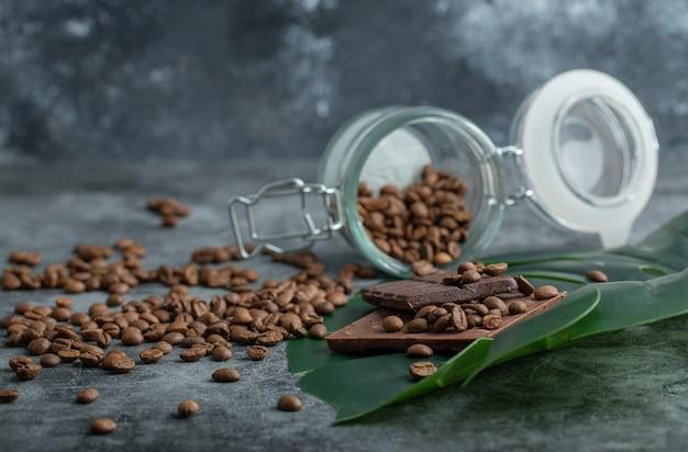 Un bocal en verre plein de grains de café avec des barres de chocolat sur un mur gris.