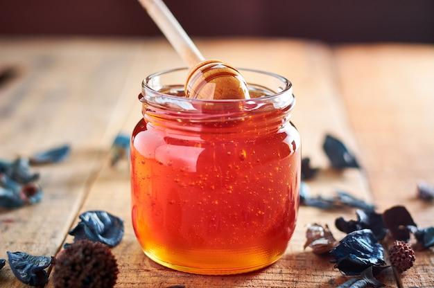 Bocal en verre plein de miel. prendre du miel avec une cuillère en bois