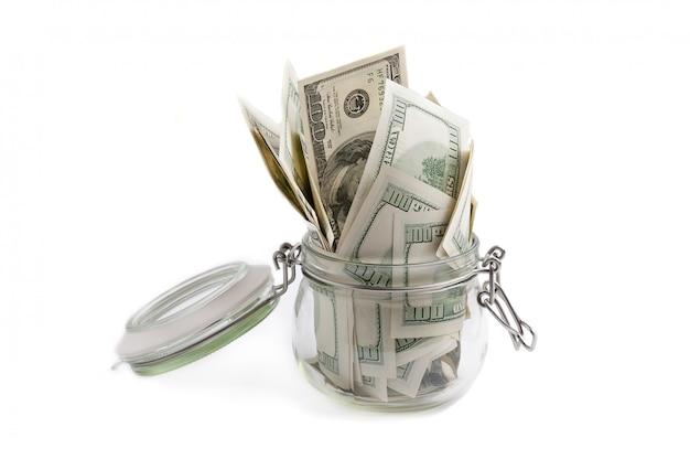 Un bocal en verre rempli de dollars parmi des billets de cent dollars.