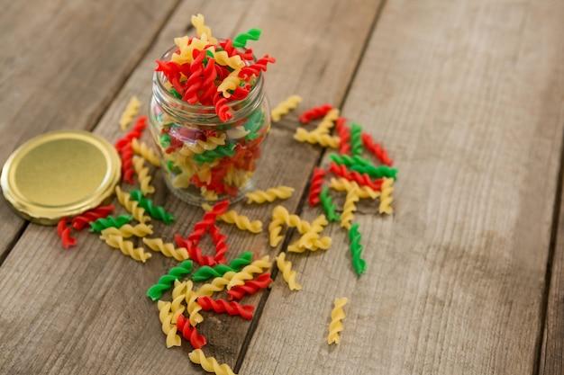 Bocal en verre rempli de pâtes rotini tricolores sur fond de bois