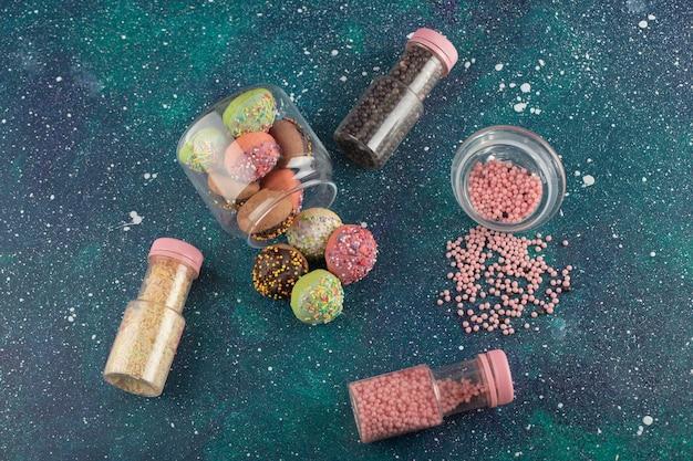 Un bocal en verre rempli de petits beignets colorés.