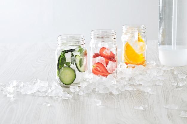 Bocaux gros plan avec de la glace et diverses garnitures orange, fraise, concombre et menthe préparés pour faire de la limonade maison fraîche avec de l'eau pétillante