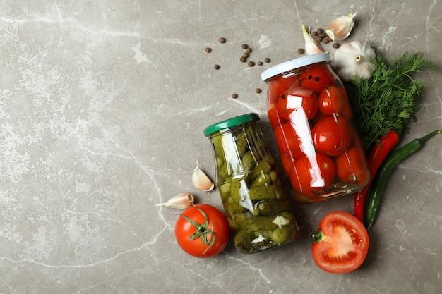 Bocaux avec légumes marinés et ingrédients sur mur gris