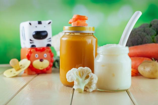 Bocaux avec purée de carottes et de chou-fleur près de légumes frais et de jouets