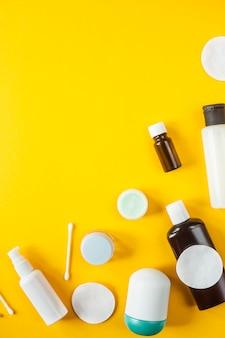 Bocaux et récipients contenant des cosmétiques, des cotons-tiges et une dispersion sur fond jaune.