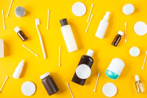 Bocaux et récipients contenant des produits cosmétiques, des cotons-tiges et une brosse à dents en coton éparpillés
