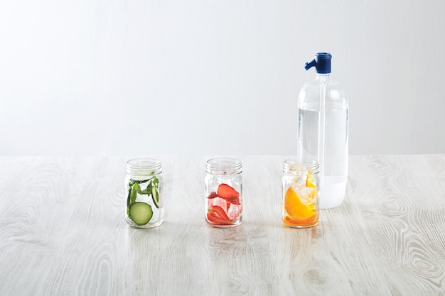 Bocaux rustiques avec de la glace et diverses garnitures. orange, fraise, concombre et menthe préparés pour faire de la limonade maison fraîche avec de l'eau pétillante de syphone.