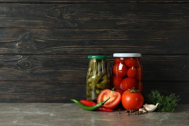 Bocaux avec tomates et concombres marinés sur mur en bois