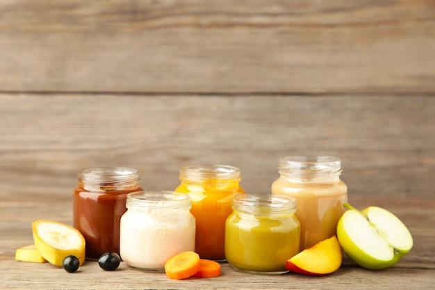 Bocaux en verre avec des aliments pour bébés et des fruits sur fond gris