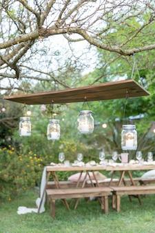 Bocaux en verre avec des bougies à l'intérieur de la décoration rustique suspendu à un bois dans un jardin
