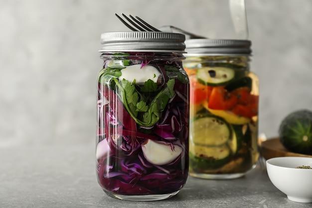 Bocaux en verre avec des légumes fermentés sur table grise