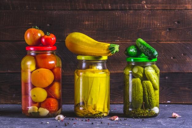 Bocaux en verre marinés maison, courgettes fraîches, concombre et tomates sur un fond en bois.