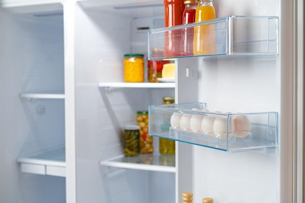 Bocaux en verre de produits en conserve sur une étagère de réfrigérateur close up