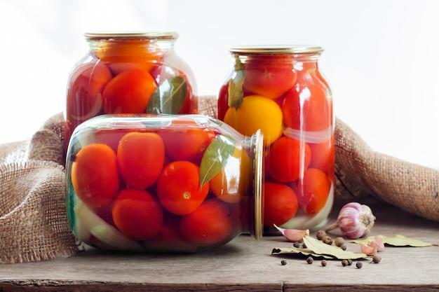 Bocaux en verre avec tomates marinées rouges, scellés avec un couvercle en métal