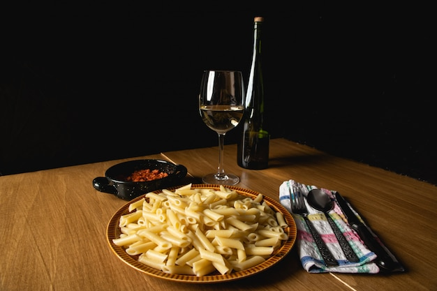 Bodegon de plat de macaronis avec sauce bolognaise et fromage râpé et un verre de vin d'accompagnement.
