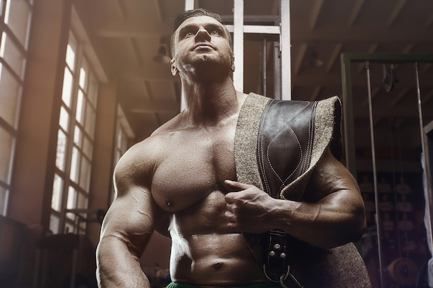 Bodybuilder à l'ancienne faisant des exercices dans une salle de gym à l'ancienne. beau style homme sportif caucasien des années 80. concept de sport, de remise en forme et d'entraînement des années 80