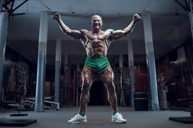 Bodybuilder athlète à l'ancienne faisant des exercices de bras dans la salle de gym. style brutal d'homme de sport caucasien chauve des années 80. concept de sport, de remise en forme et d'entraînement des années 80