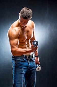Le bodybuilder d'athlète masculin tient l'haltère dans la main. muscles de pompage. torse nu.