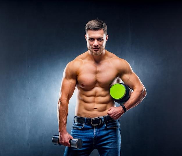 Le bodybuilder d'athlète masculin tient un pot de nutrition sportive et d'haltère dans les mains. posant à la caméra pose sur fond bleu.