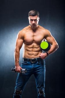 Le bodybuilder d'athlète masculin tient un pot de nutrition sportive et d'haltère dans les mains.