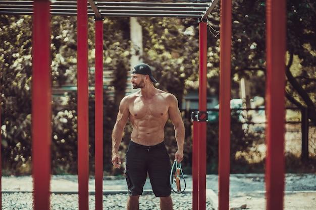 Bodybuilder Barbu Homme Exerçant Sur Des Barres De Singe Pour Le Haut Du Corps Dans Un Parc De Gymnastique Moderne à L'extérieur Par Une Journée Ensoleillée Photo Premium
