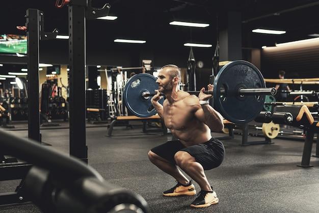 Bodybuilder barbu pendant son entraînement avec une barre dans la salle de gym