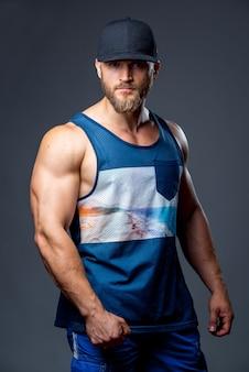 Bodybuilder barbu vêtu d'un débardeur.