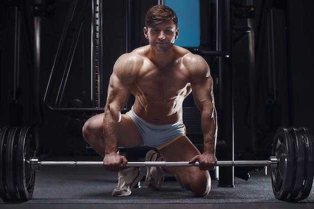 Bodybuilder bel homme athlétique fort à côté d'une barre. fitness d'entraînement et concept sain de musculation
