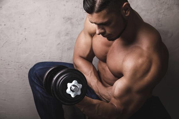 Bodybuilder brutal massif faisant des exercices de flexion des biceps avec l'haltère