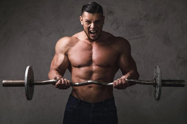 Bodybuilder Brutal Massif Faisant Des Exercices Pour Les Biceps Avec La Barre Photo Premium