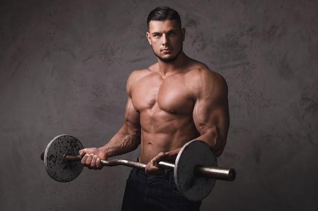 Bodybuilder brutal massif faisant des exercices pour les biceps avec la barre