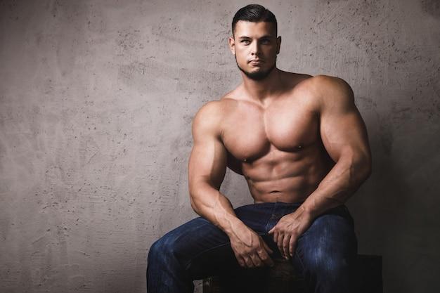 Bodybuilder brutal massif posant à côté du mur de béton