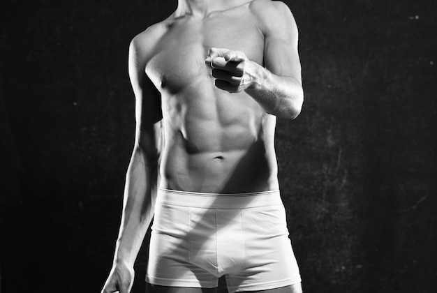 Bodybuilder avec un corps gonflé en culotte blanche posant sur fond sombre